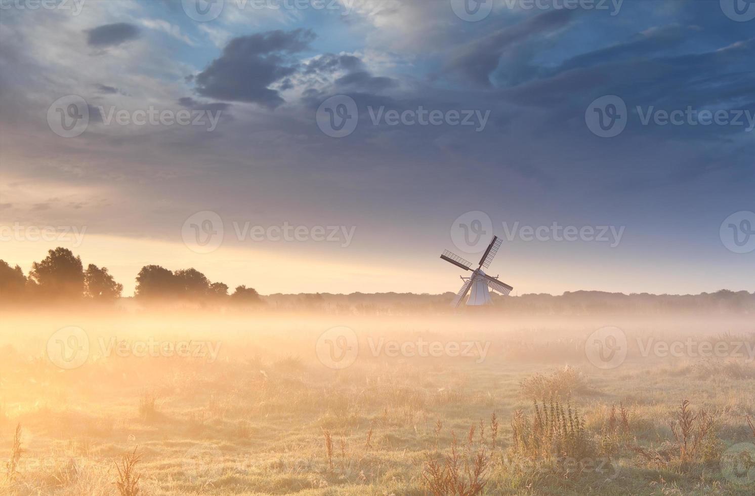 moinho de vento no nevoeiro ao nascer do sol foto
