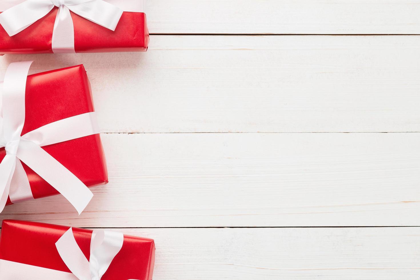 decoração de caixas de presente de natal vermelha em mesa de madeira branca foto