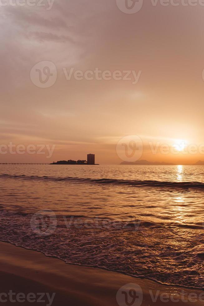 silhueta de construção em frente a um enorme pôr do sol rosa foto