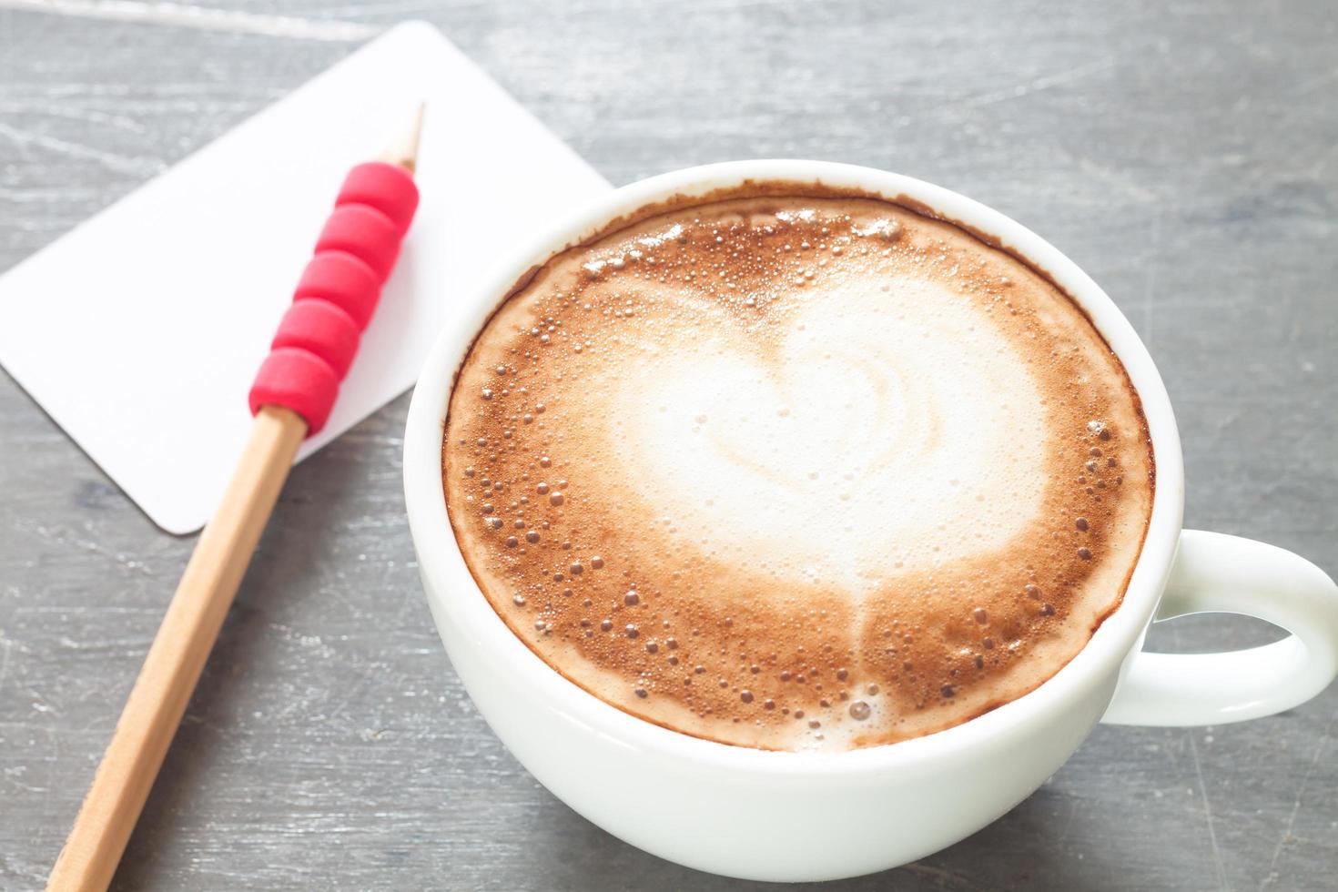 café com leite com um cartão de visita e lápis foto