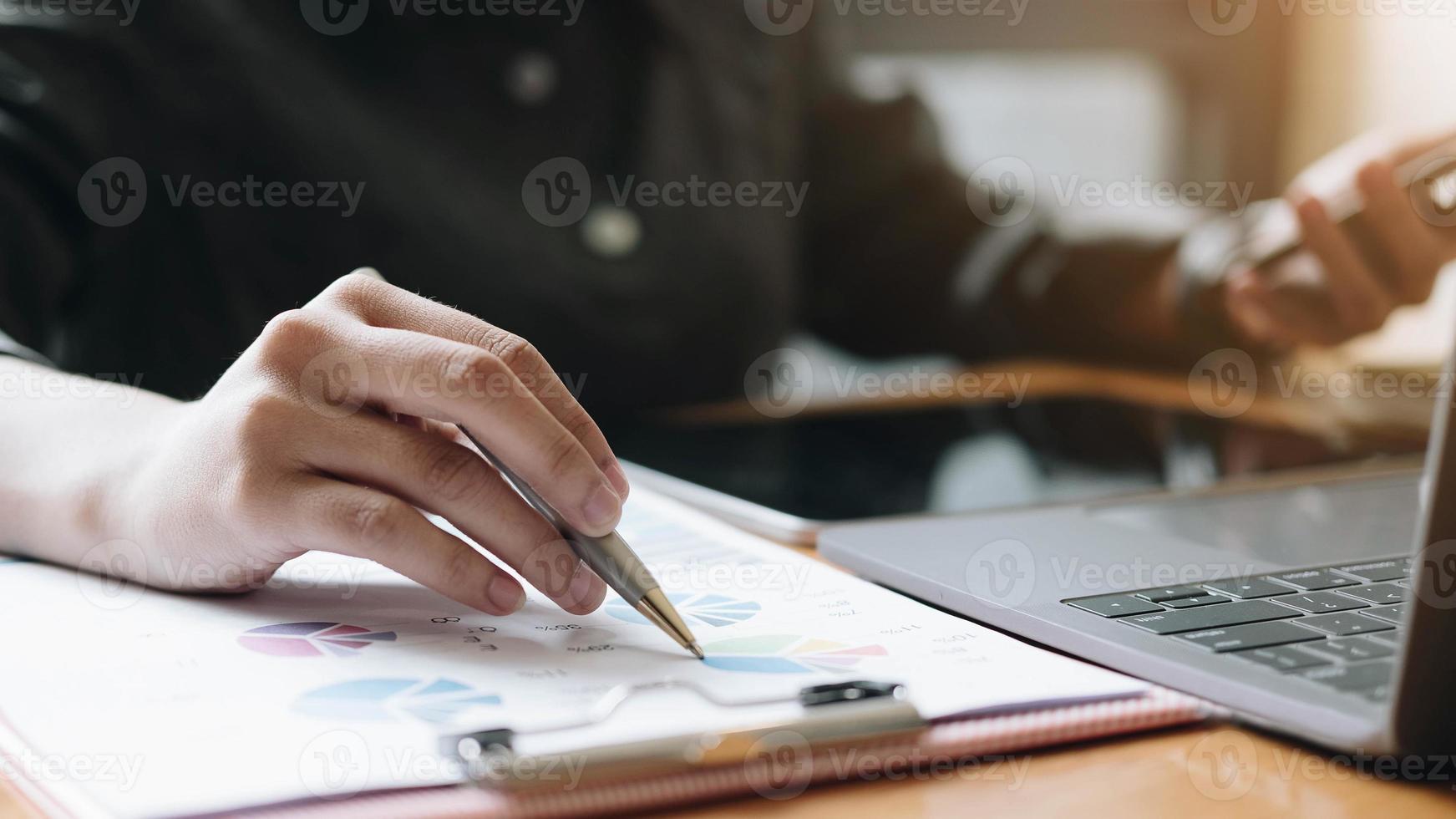 empresário trabalhando com gráficos de documentos na mesa do escritório foto