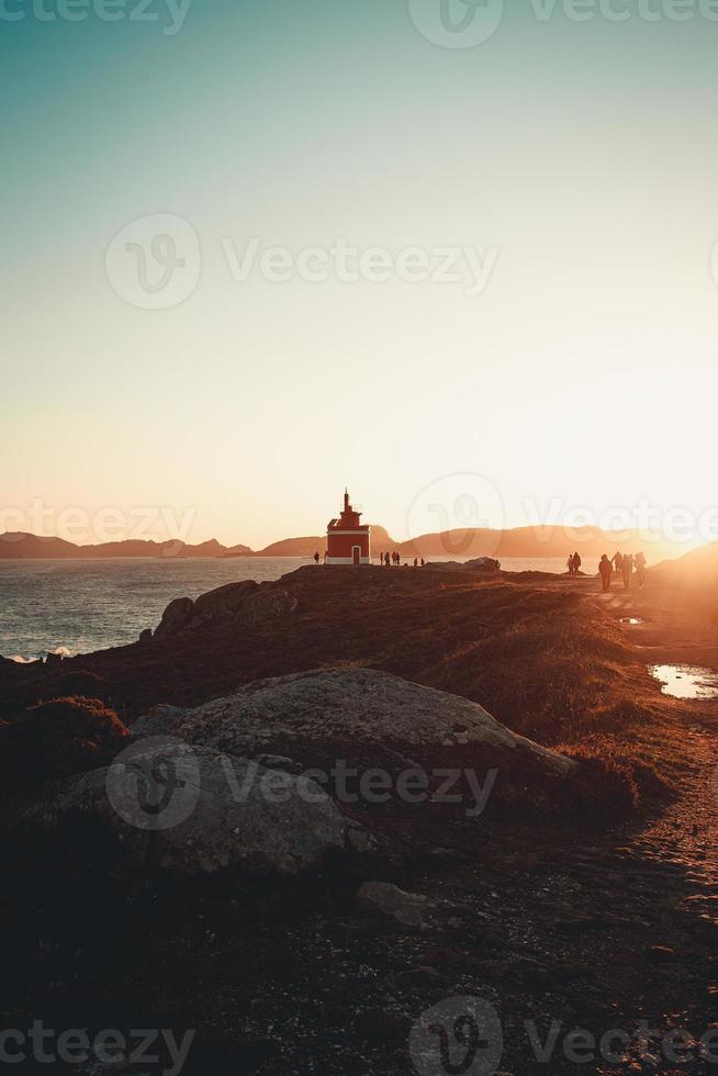 um farol vermelho sob um grande pôr do sol foto