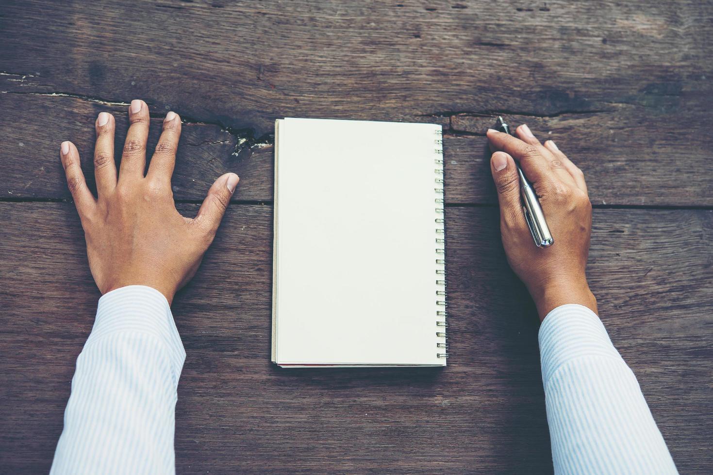 homem escrevendo no caderno em branco na mesa de madeira foto