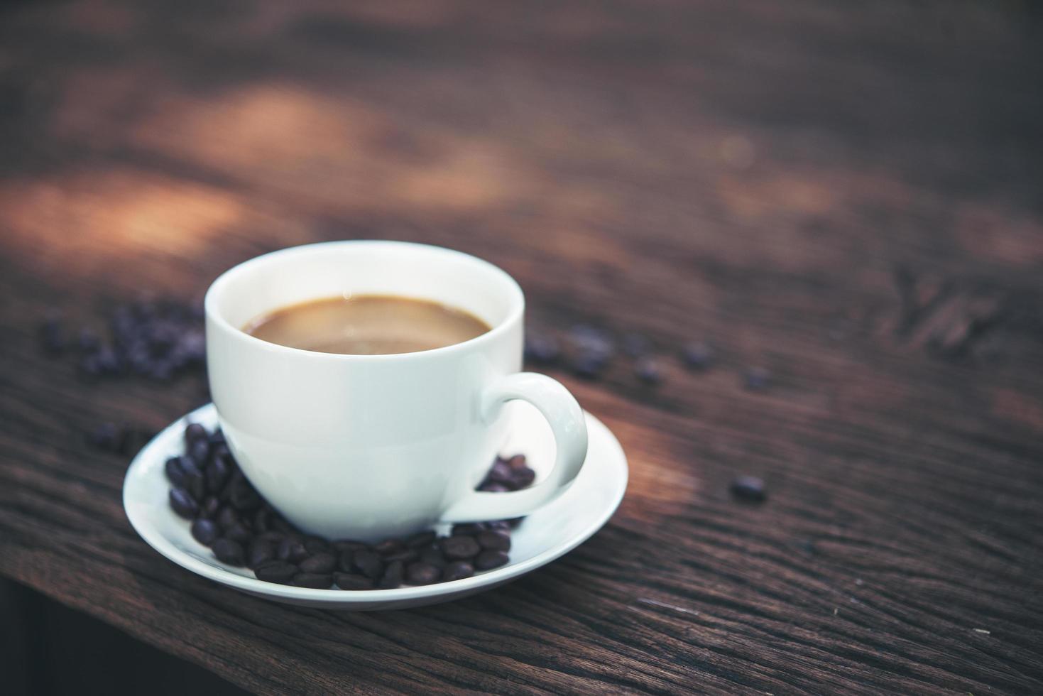 close-up de uma xícara de café com grãos de café na mesa de madeira foto