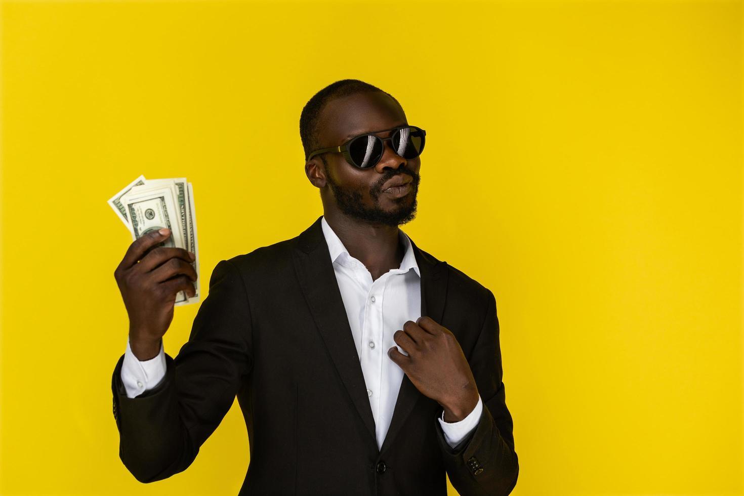 homem de terno e óculos escuros segurando dinheiro foto