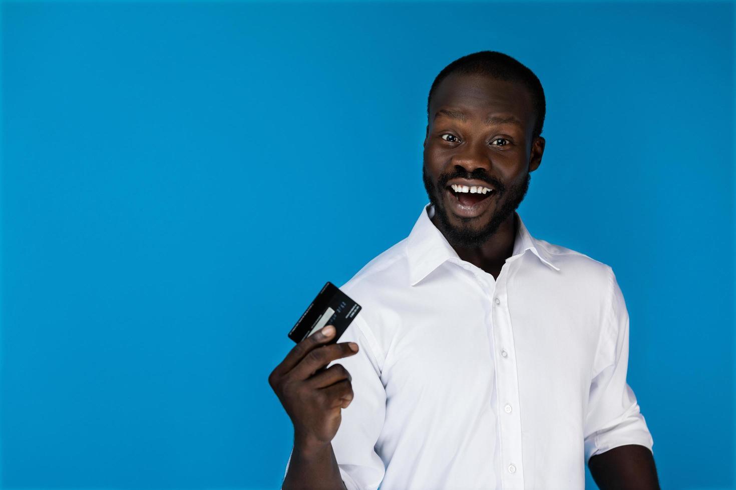homem sorridente com um cartão de crédito foto