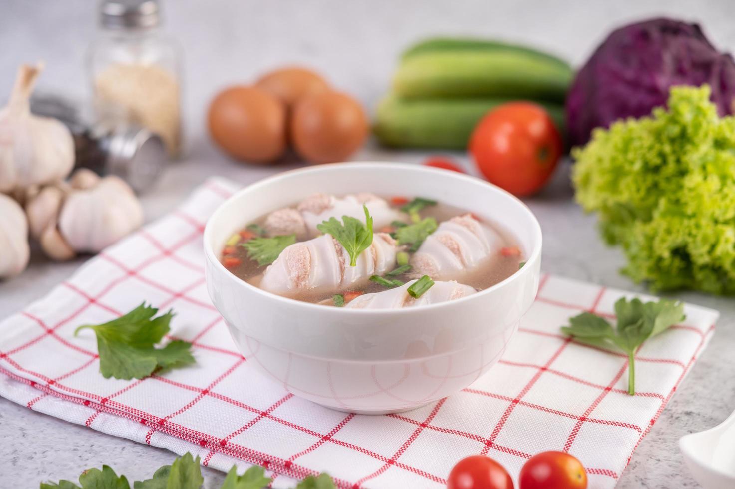 tigela branca de sopa de lula com porco e cebolinha foto