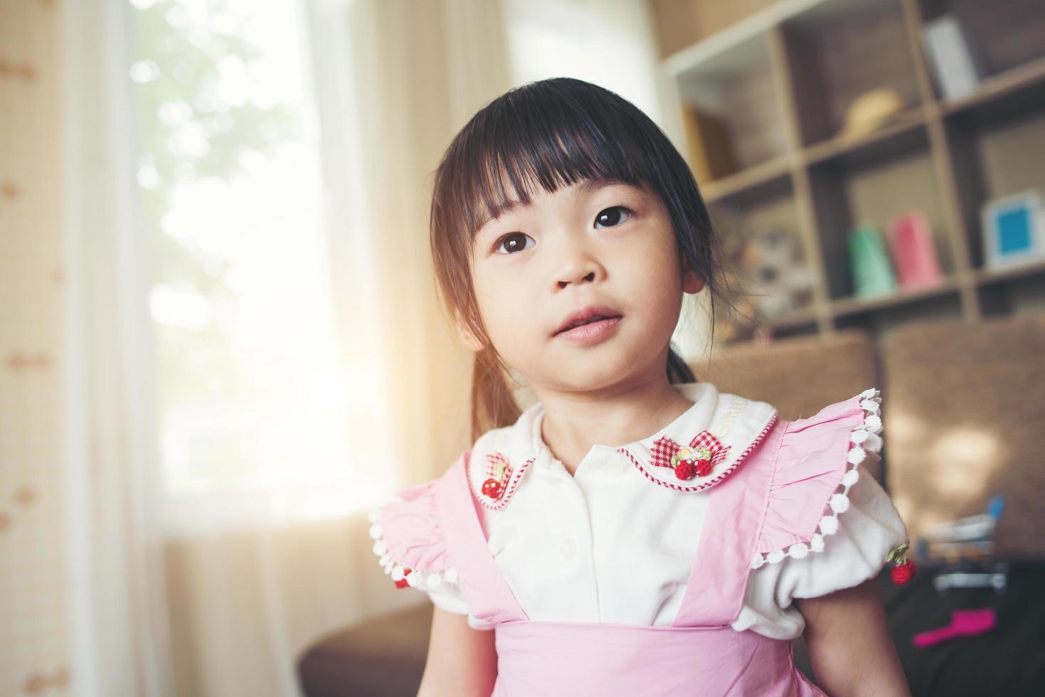 retrato de uma menina asiática brincando em sua casa foto