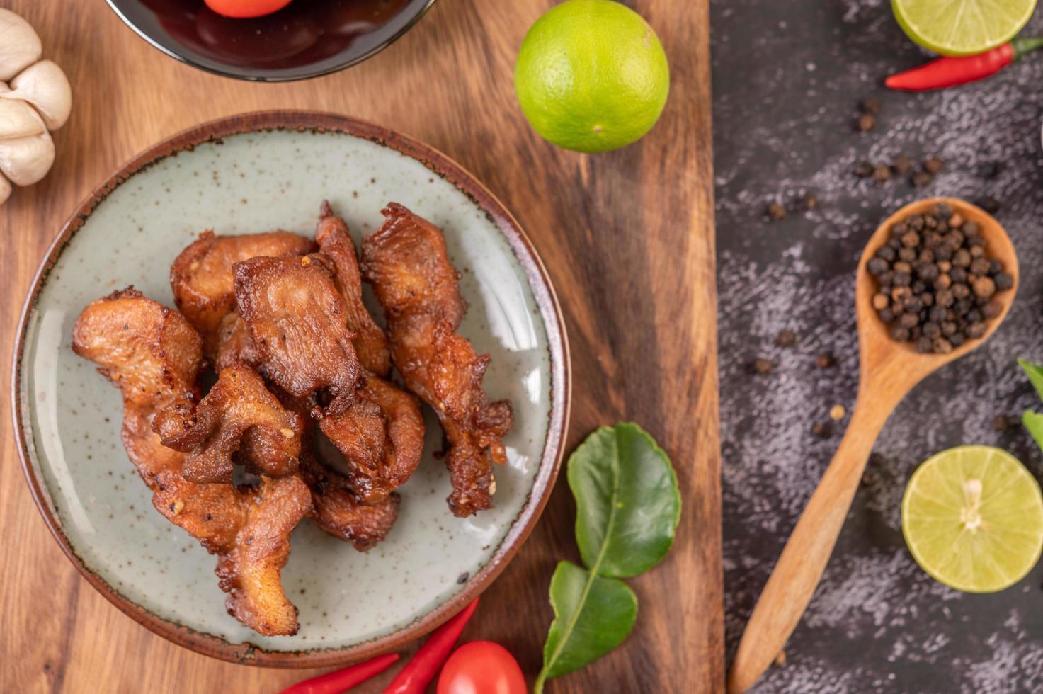 Costeleta de porco em um prato branco na mesa preta foto