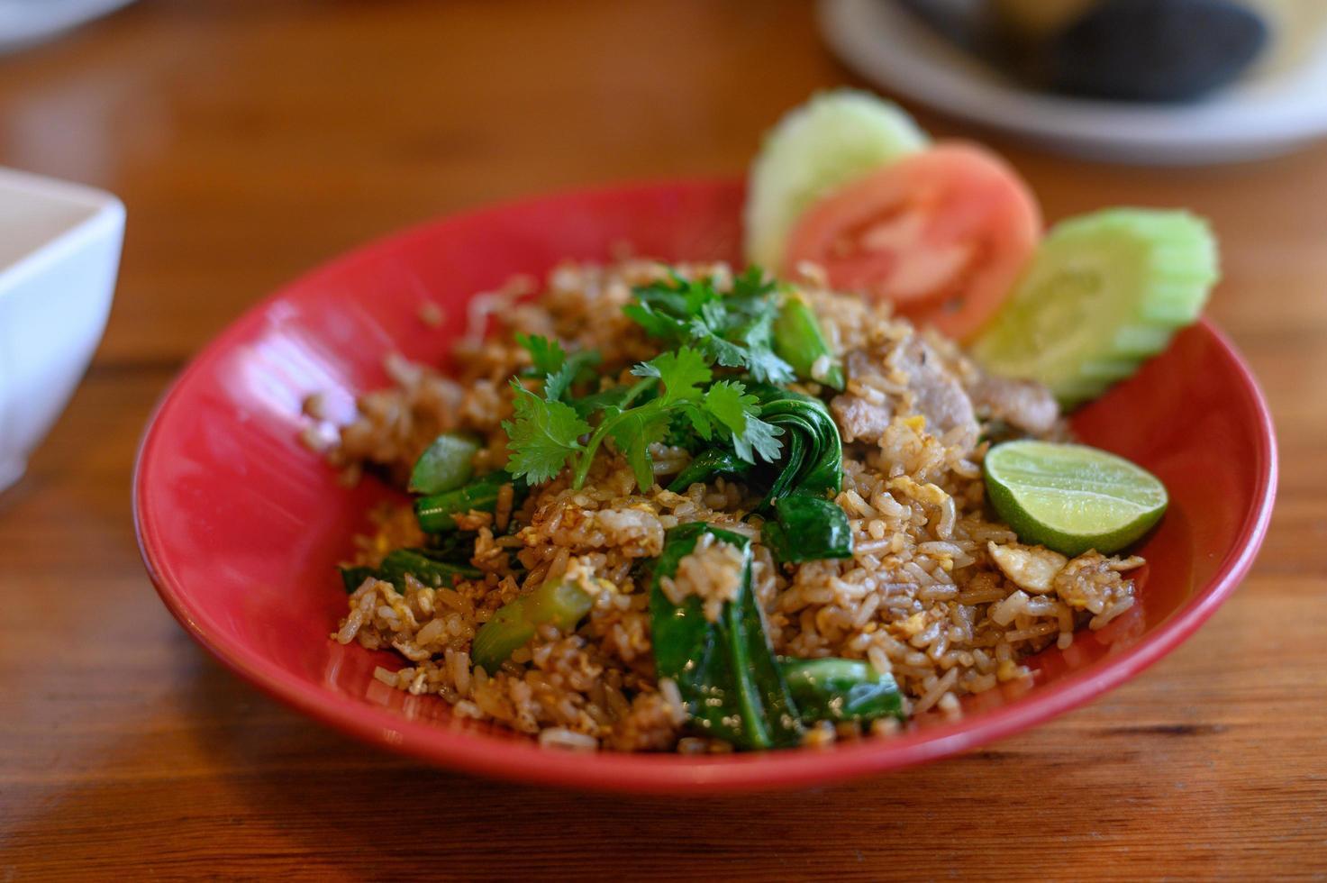 arroz de porco frito que está no prato, com meio limão na mesa de madeira foto