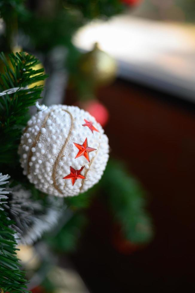 close-up de uma bola branca pendurada na árvore de natal foto