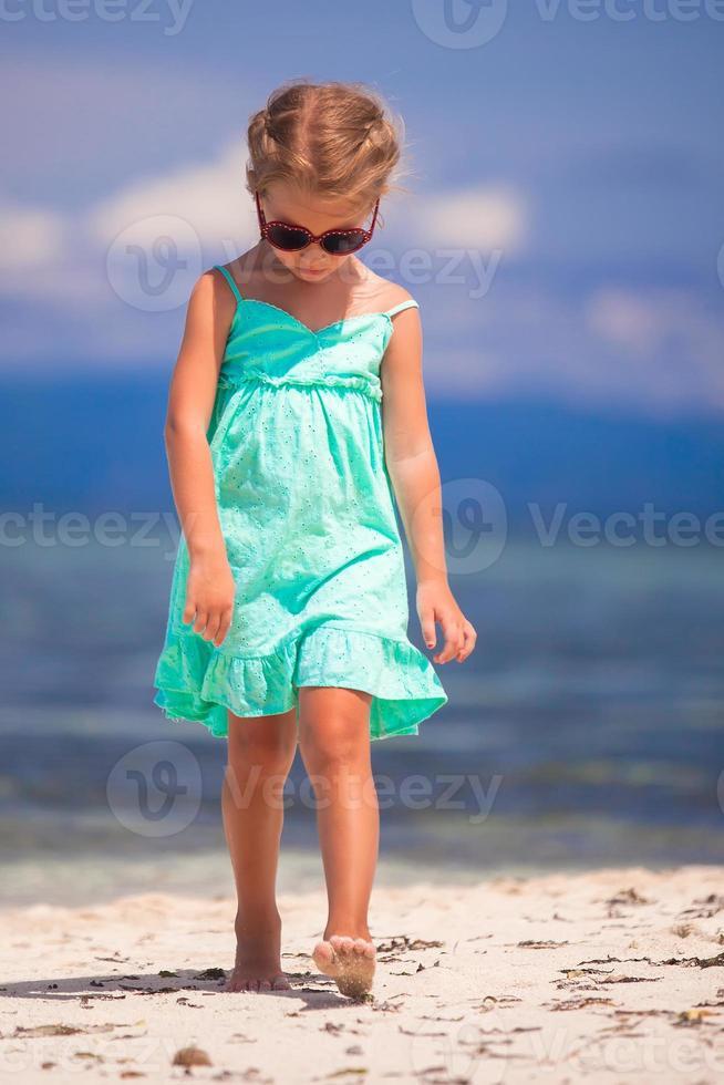 adorável garotinha caminhando na praia tropical branca foto