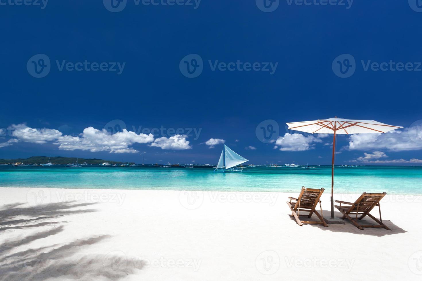 guarda-sóis e camas de madeira em praia tropical foto