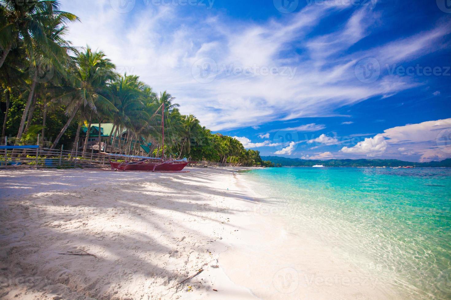 praia tropical com areia branca e um pequeno barco foto