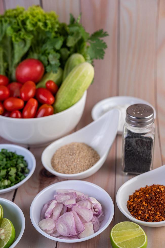 Pedaços de frango cozido com legumes e temperos em uma mesa de madeira foto