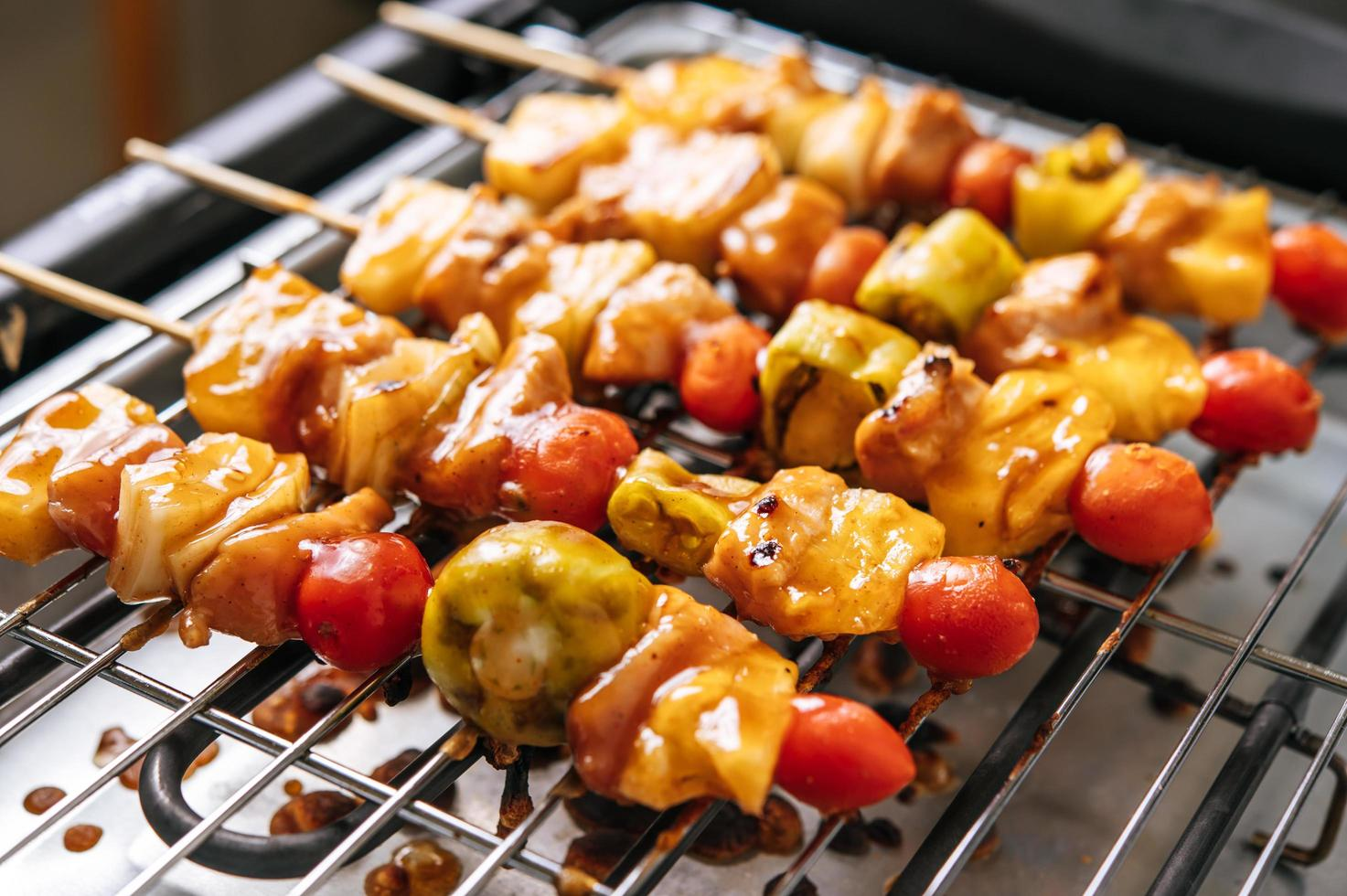 churrasqueira com variedade de carnes, tomate e pimentão foto