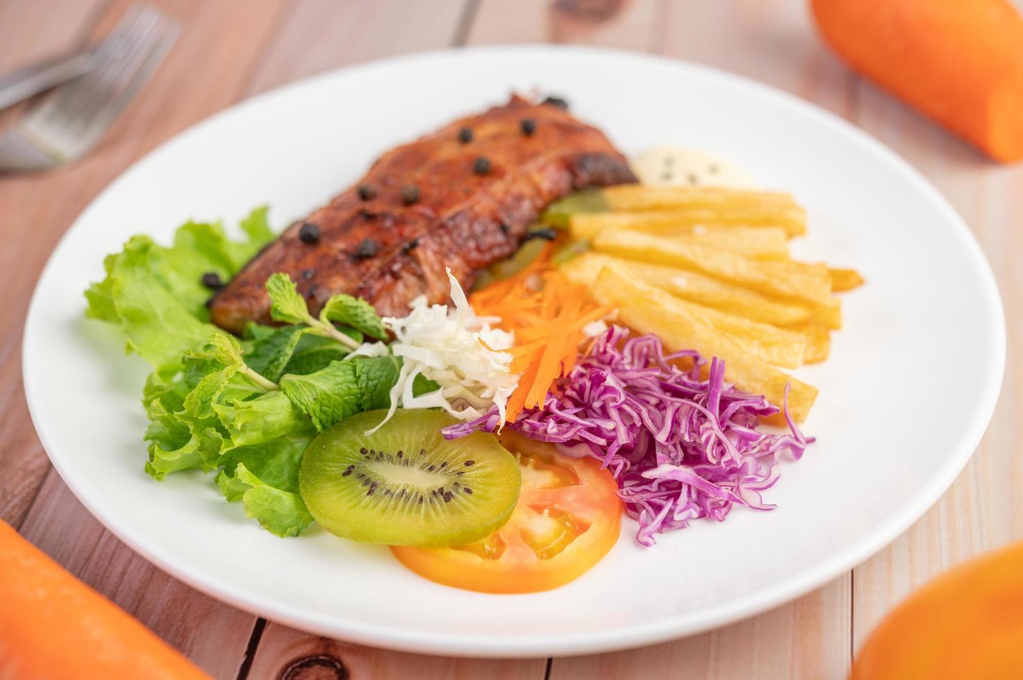 bife de peixe com batata frita e salada foto