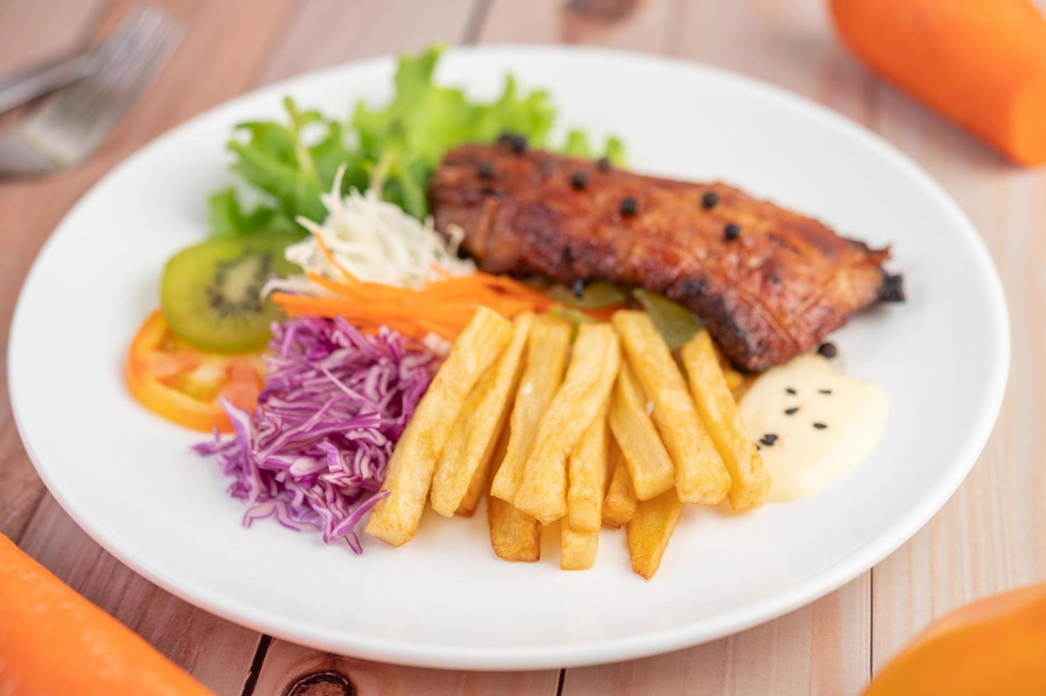 bife de peixe com batata frita, frutas e vegetais foto