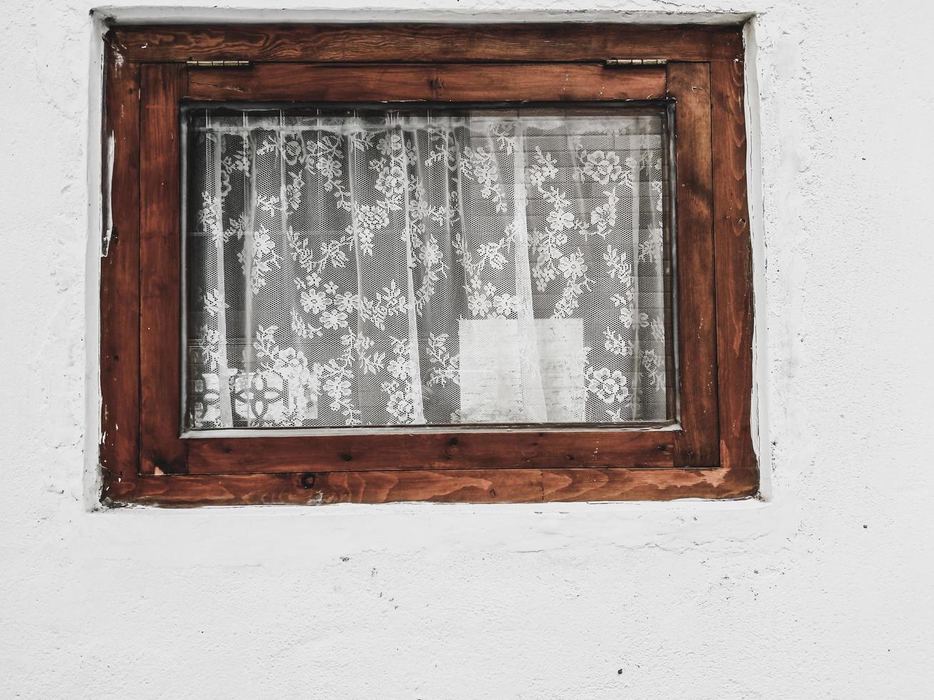 janela rústica com cortinas de renda branca. parede de cimento grunge com janela vintage foto