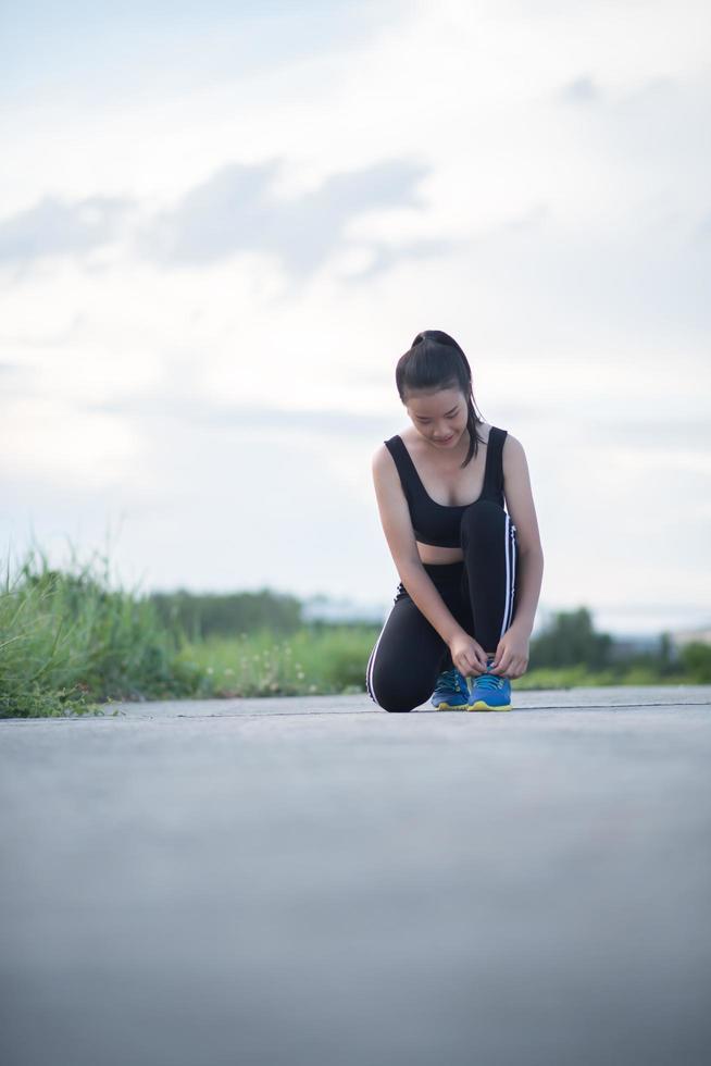 jovem corredor amarrando seus sapatos ao ar livre foto