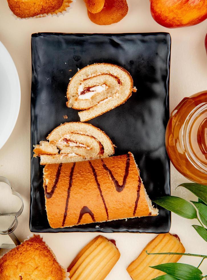 vista superior do rolo cortado e fatiado em um prato com biscoitos de bolinho de geléia de pêssego no fundo branco foto