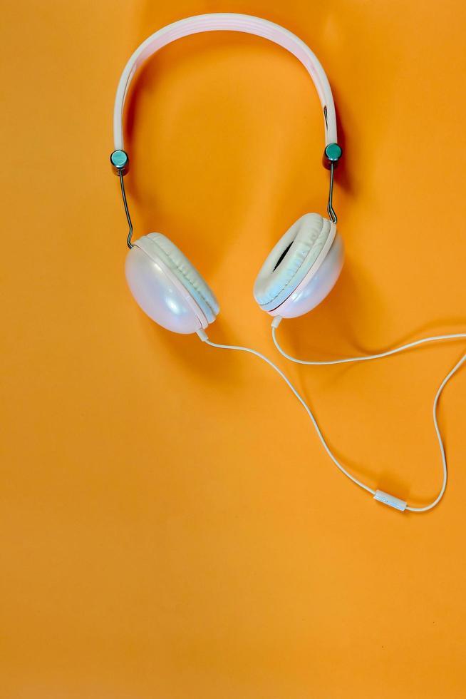 auscultadores musicais em fundo laranja foto
