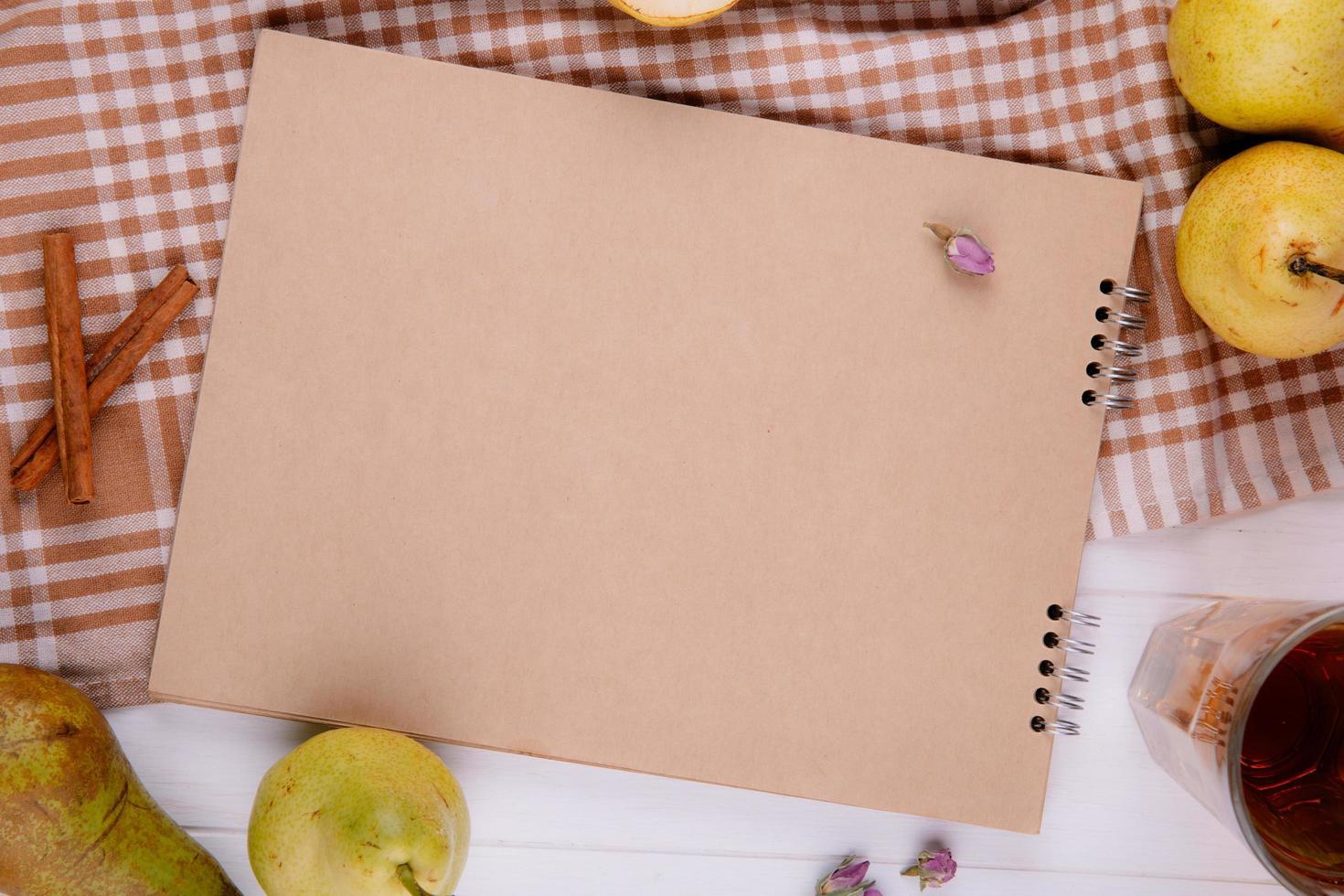 vista superior do caderno de desenho feito de papel artesanal com peras frescas maduras na toalha de mesa xadrez foto