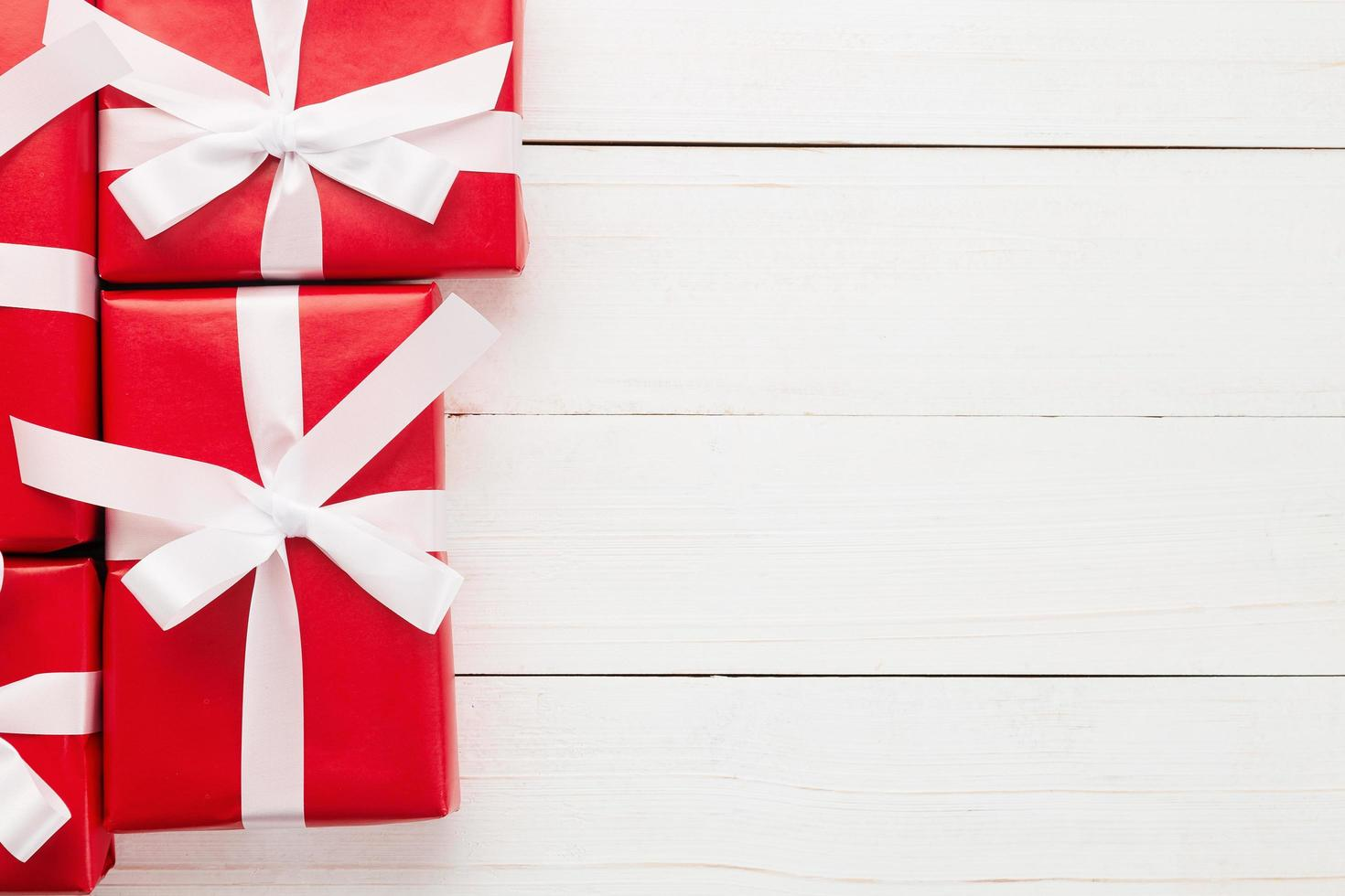 Natal e ano novo com decoração de caixas de presente vermelhas na vista superior de fundo de mesa de madeira branca com espaço de cópia foto