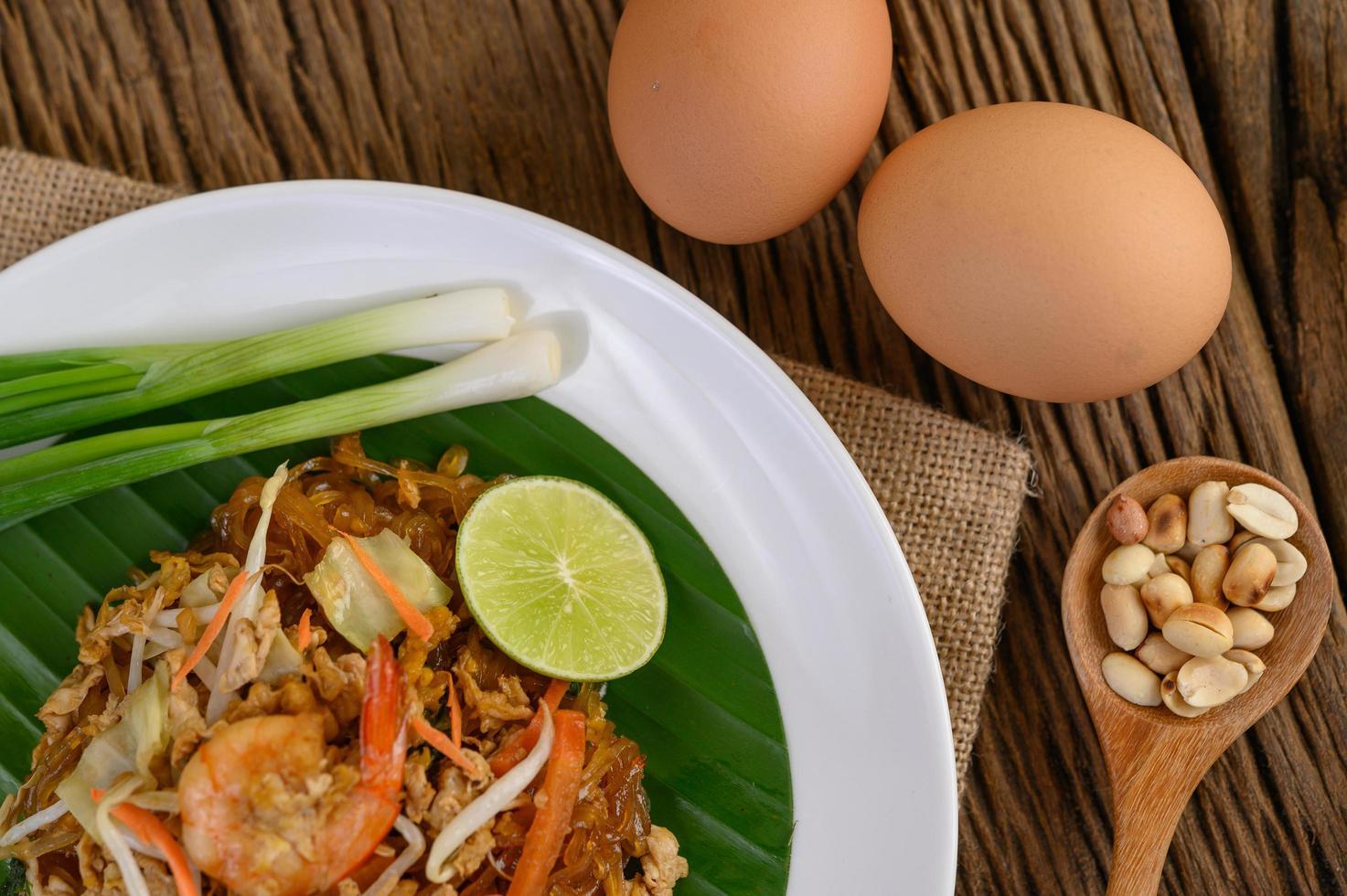 prato de camarão pad thai com limão e ovos foto