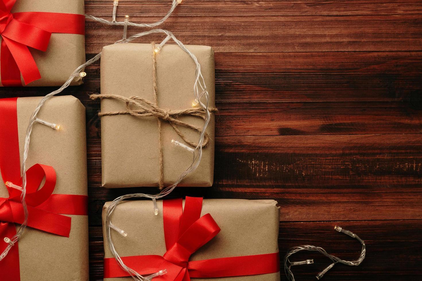 Natal e ano novo com caixas de presente e decoração de luz de corda na vista superior do fundo da mesa de madeira com espaço de cópia foto