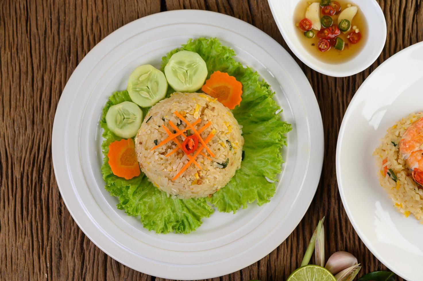 arroz frito em um prato branco com alface e enfeite foto