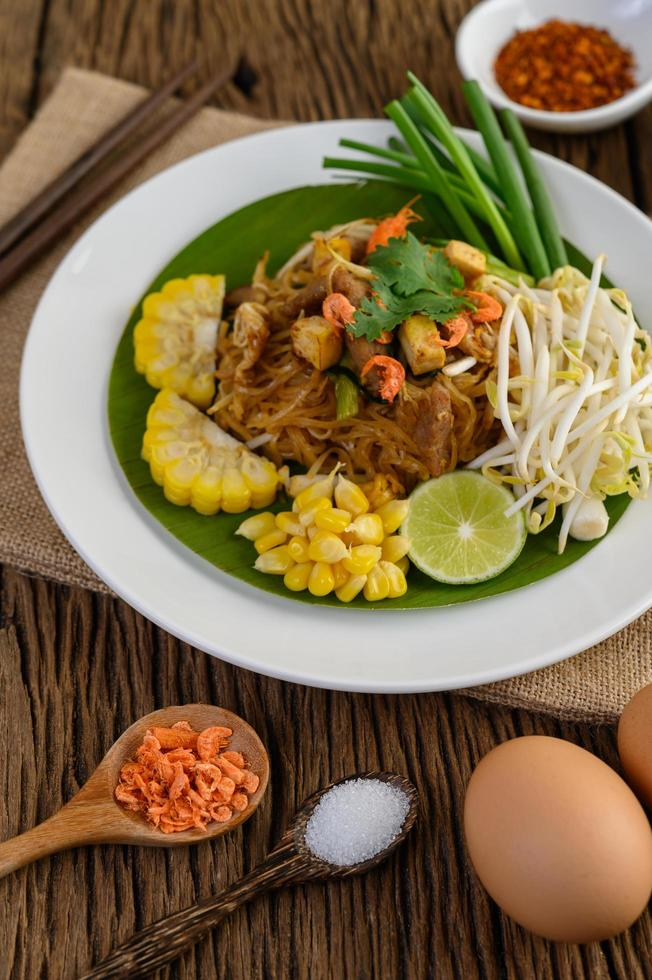 Pad thai com limão, ovos e temperos em uma mesa de madeira foto
