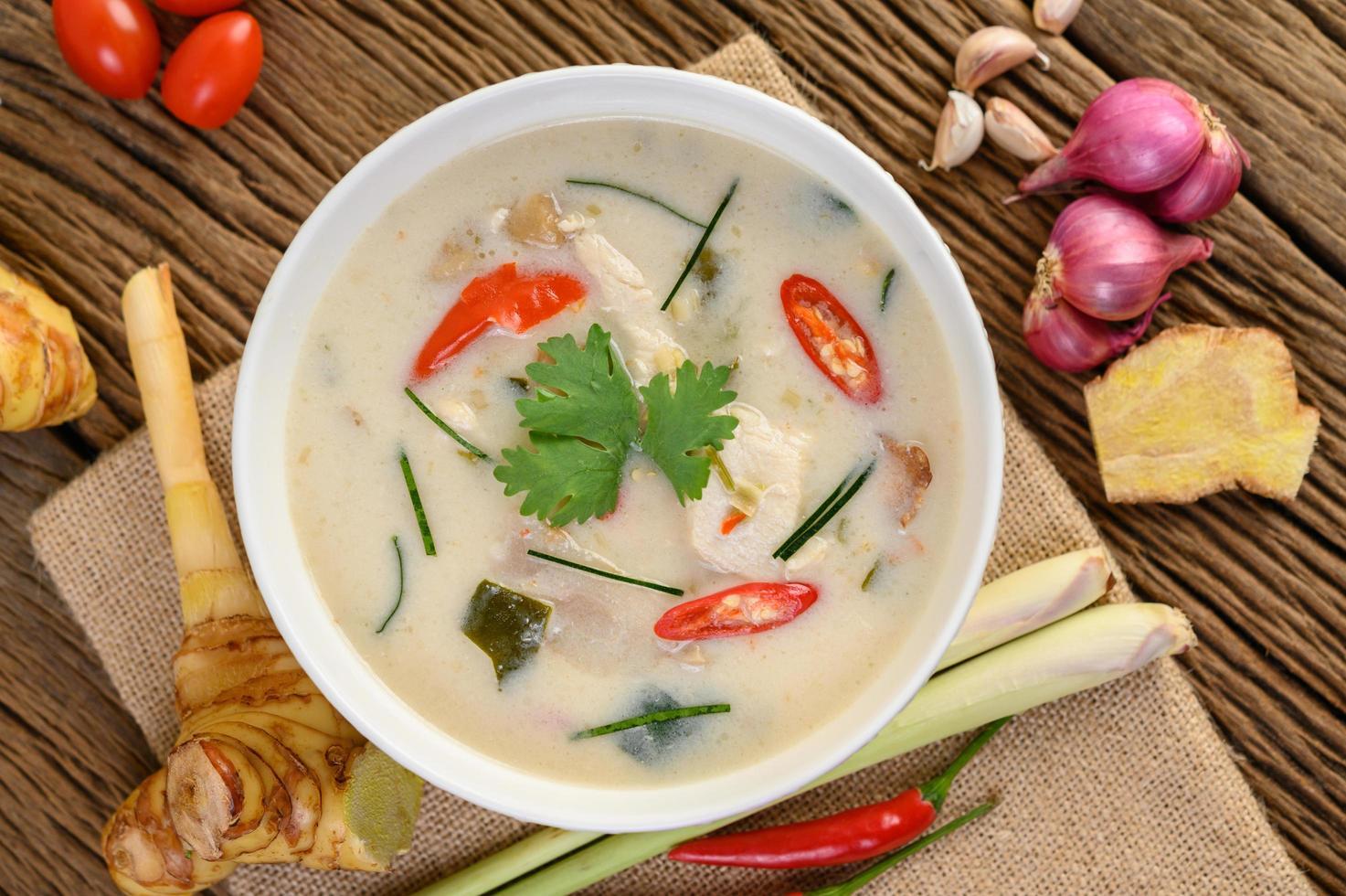 tom kha kai, sopa de coco tailandesa na mesa de madeira da cozinha foto