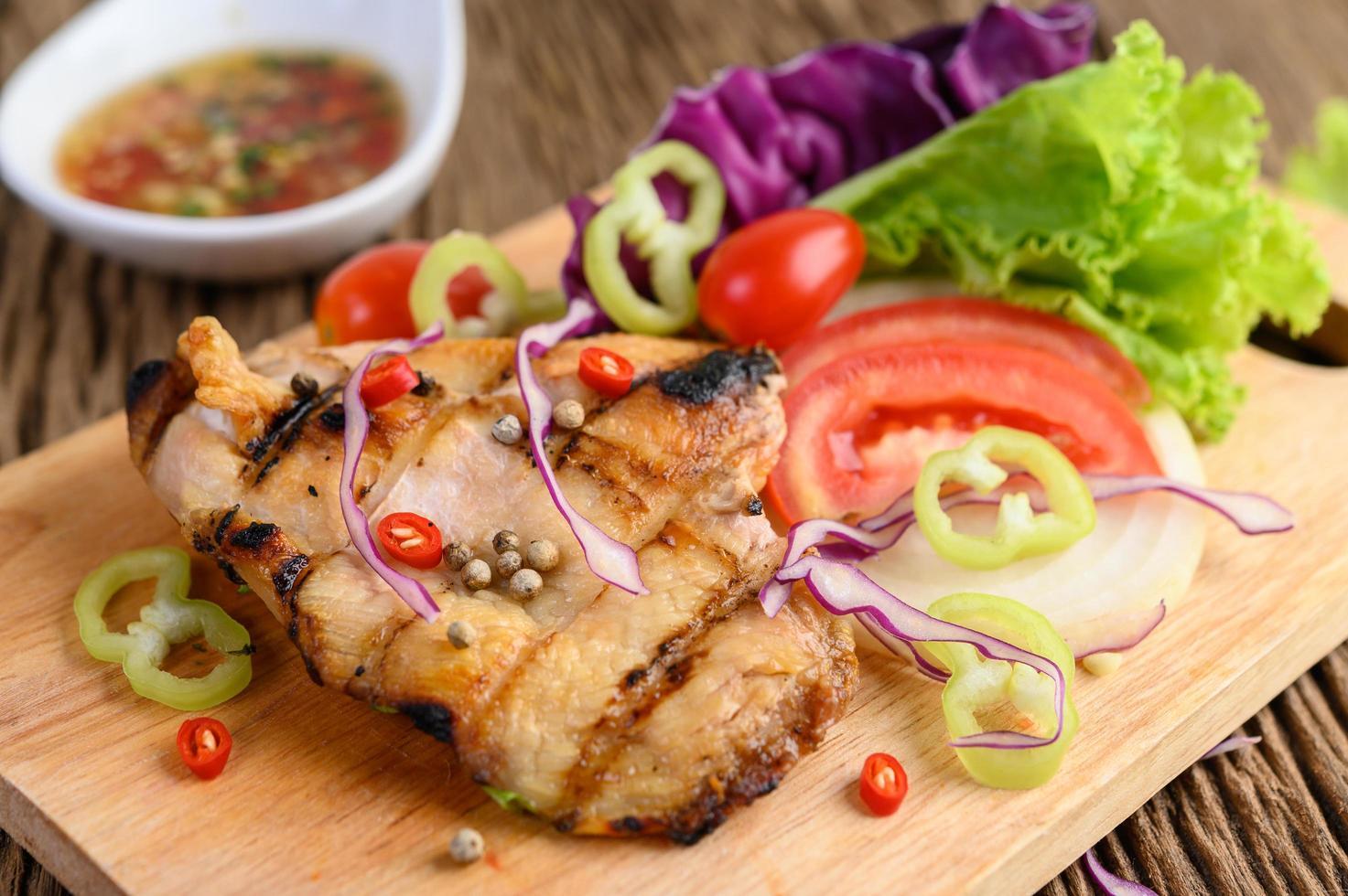 frango grelhado em uma tábua de madeira com salada foto