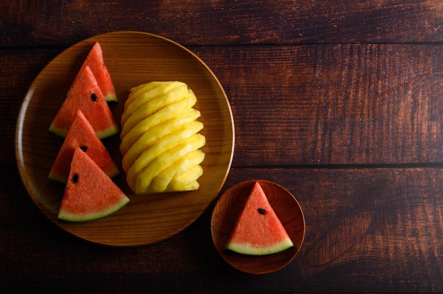 fatias de melancia e abacaxi na mesa de madeira escura foto