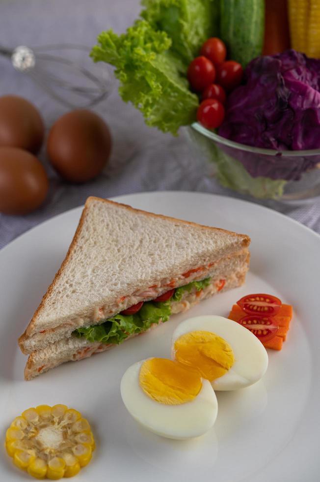 Ovos cozidos, milho, sanduíche de tomate em um prato branco foto