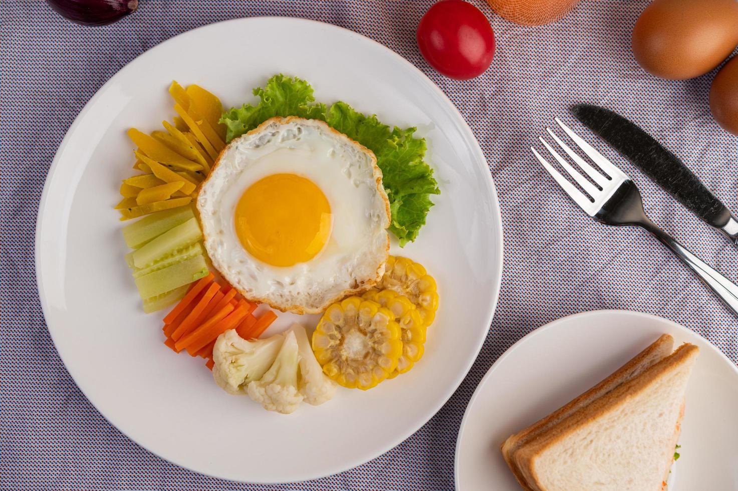 ovo frito café da manhã com ovo, salada, abóbora, pepino, cenoura e milho foto