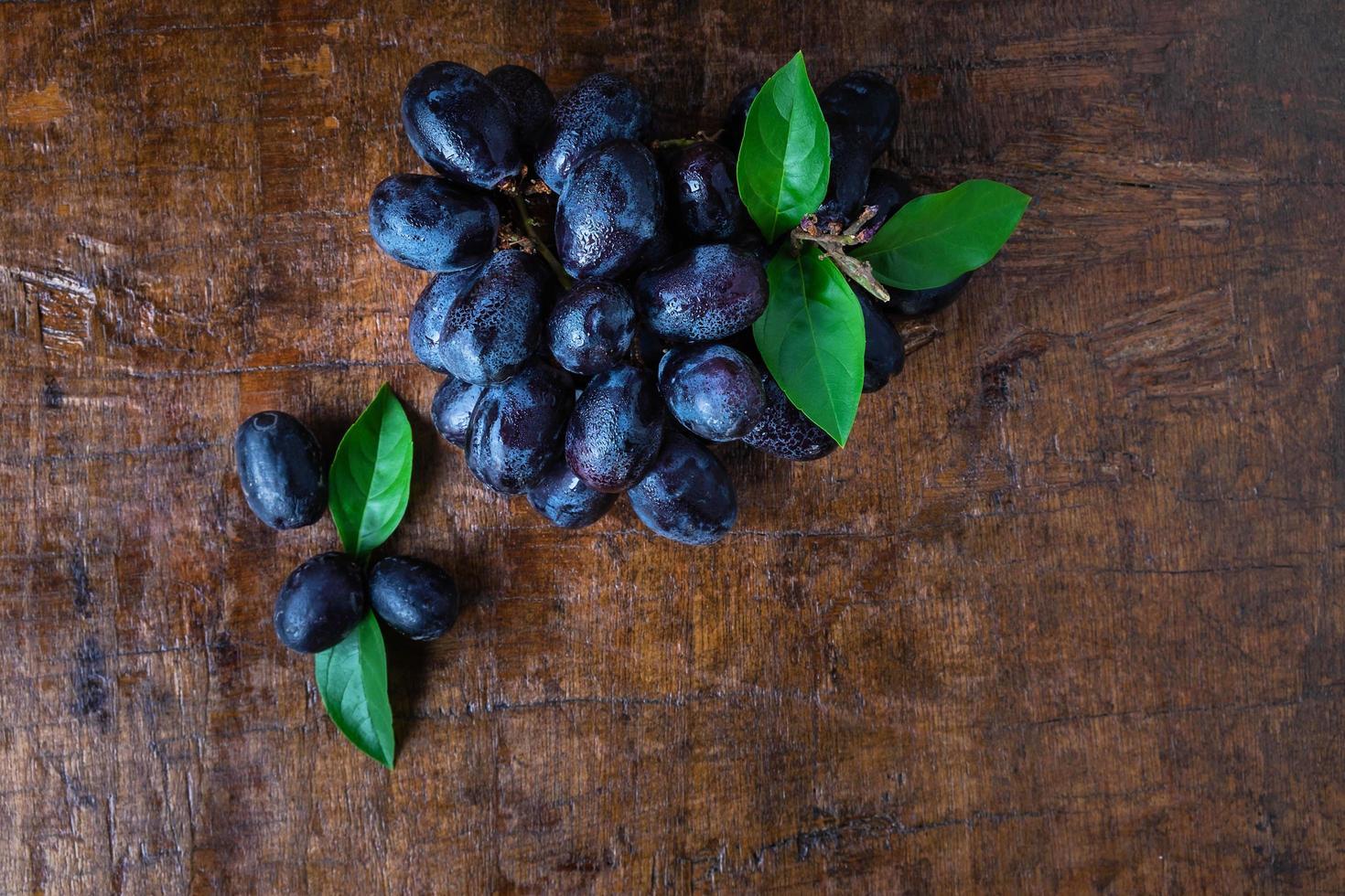 uvas pretas em uma mesa de madeira foto