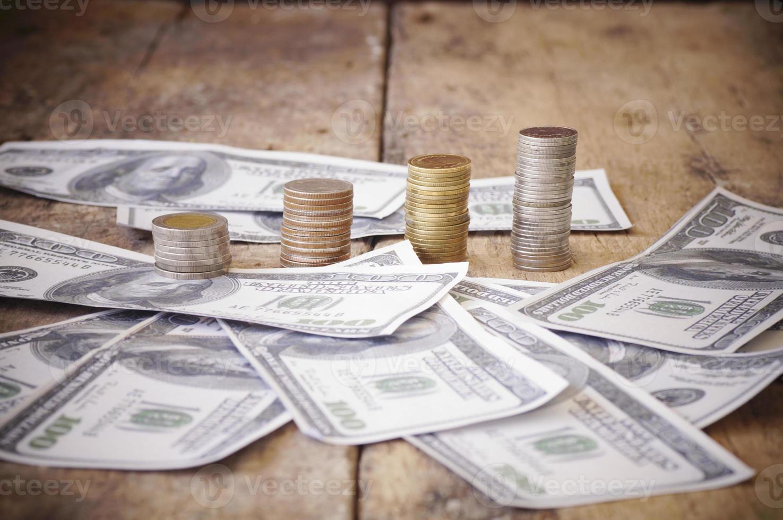moedas e dinheiro em uma mesa de madeira foto