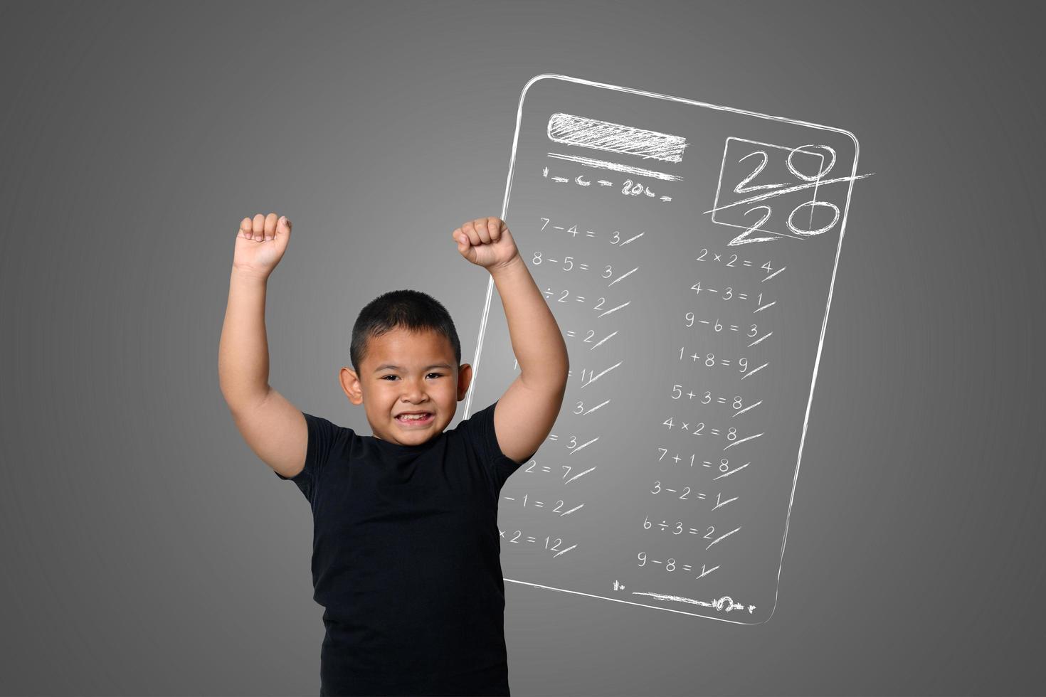 menino mostra nota máxima em testes escolares na lousa foto