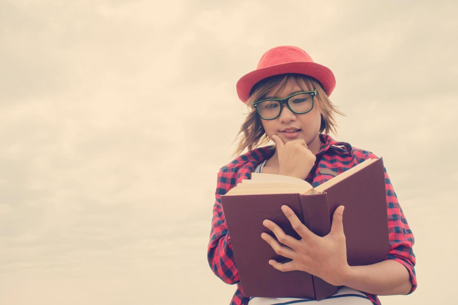 mulher jovem hippie segurando um livro abaixo do céu foto