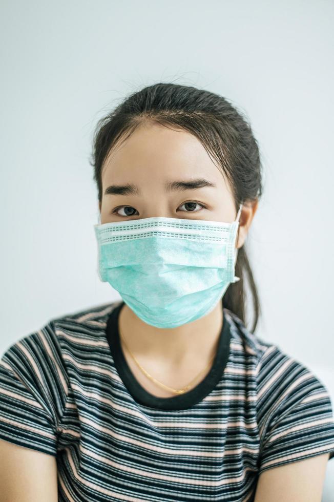 uma mulher vestindo uma camisa listrada e uma máscara protetora foto