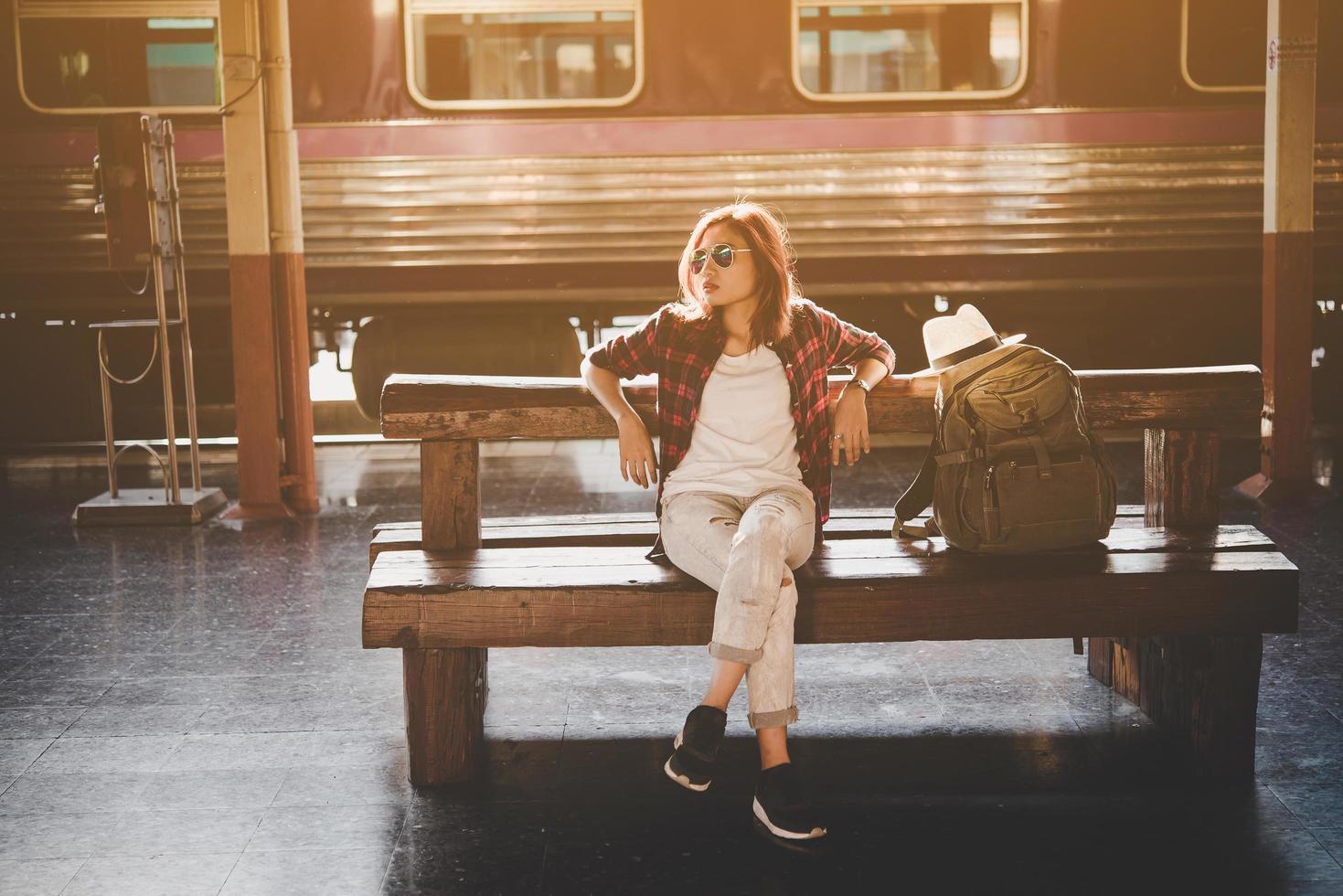 jovem hippie turista com mochila sentada na estação de trem foto