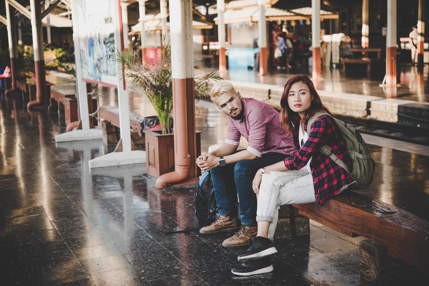 casal jovem hippie sentado em um banco de madeira na estação de trem foto