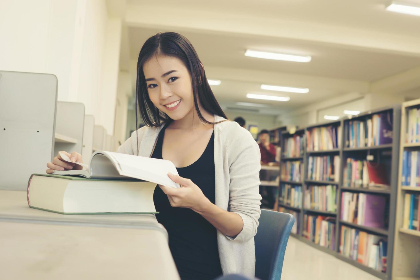 jovem estudante asiática na biblioteca lendo um livro foto