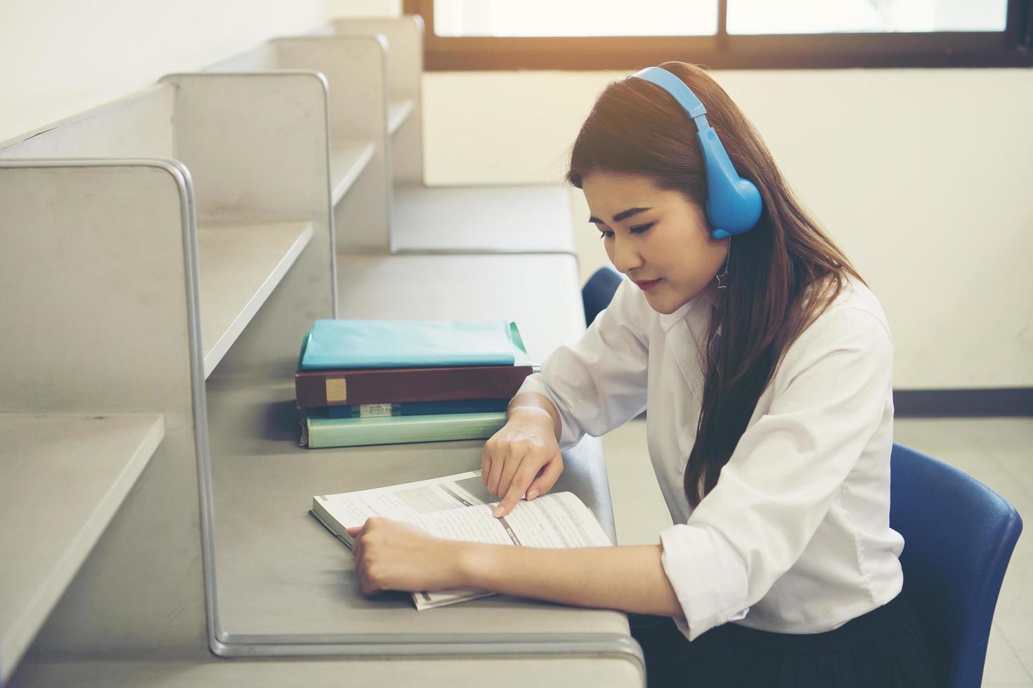 jovem estudante asiática lendo na biblioteca foto