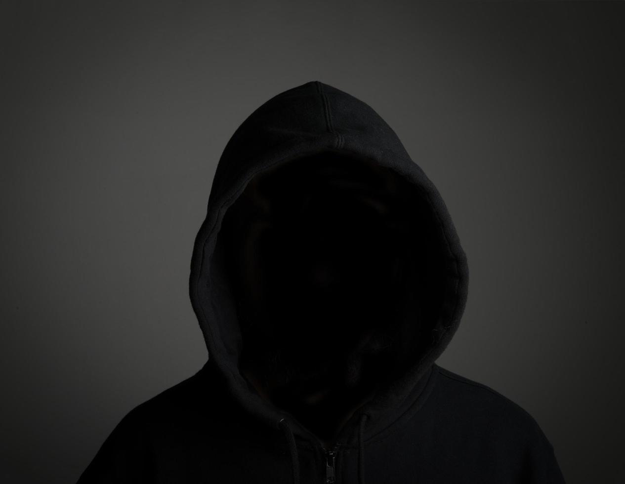 jovem hacker sem rosto em fundo preto foto