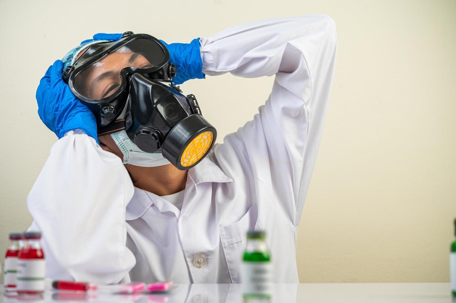 cientista usando luvas e segurando copos foto