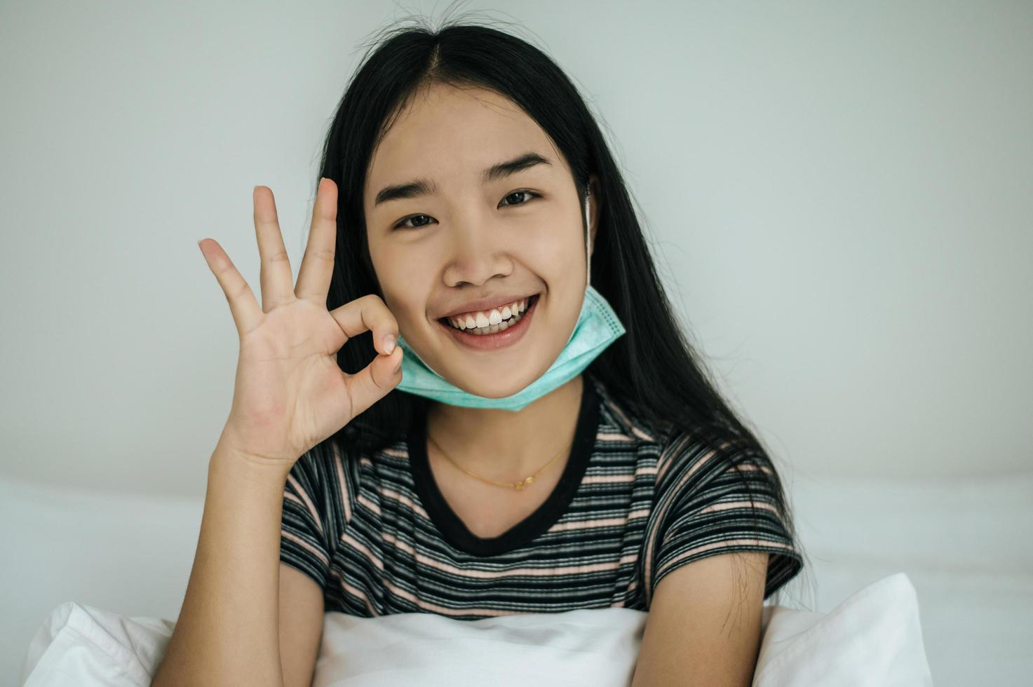 garota usando máscara higiênica, camisa listrada e símbolo de mão ok foto