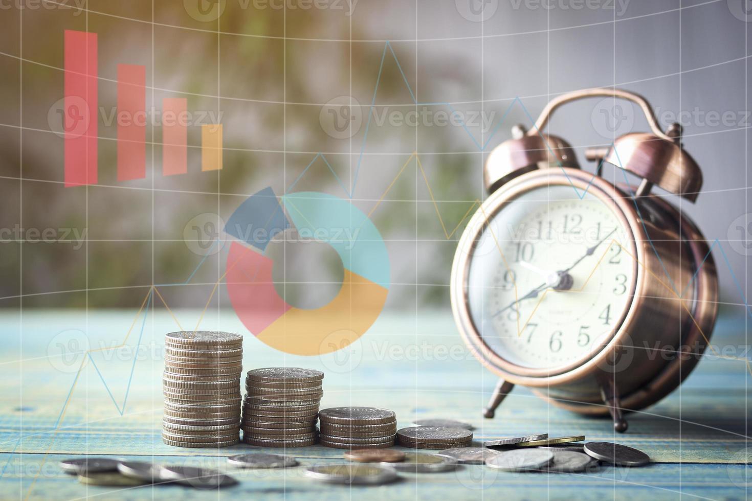 despertador e pilhas de moedas com sobreposição de gráfico foto